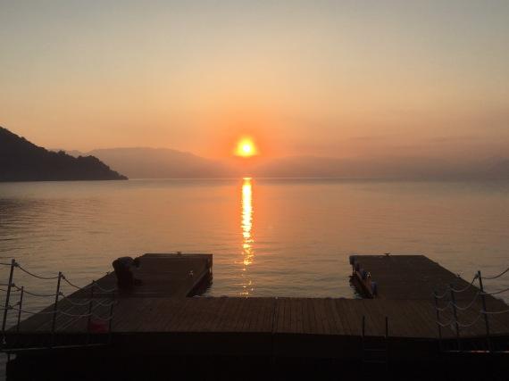 The sun just rising above the horizon on Lake Atitlan